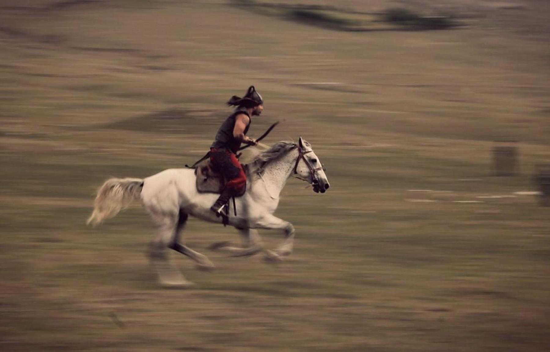 Gnający na swoim koniu Kirgiski wojownik. Zdjęcie zrobione podczas festiwalu nomadów nad Issyk-Kulem.