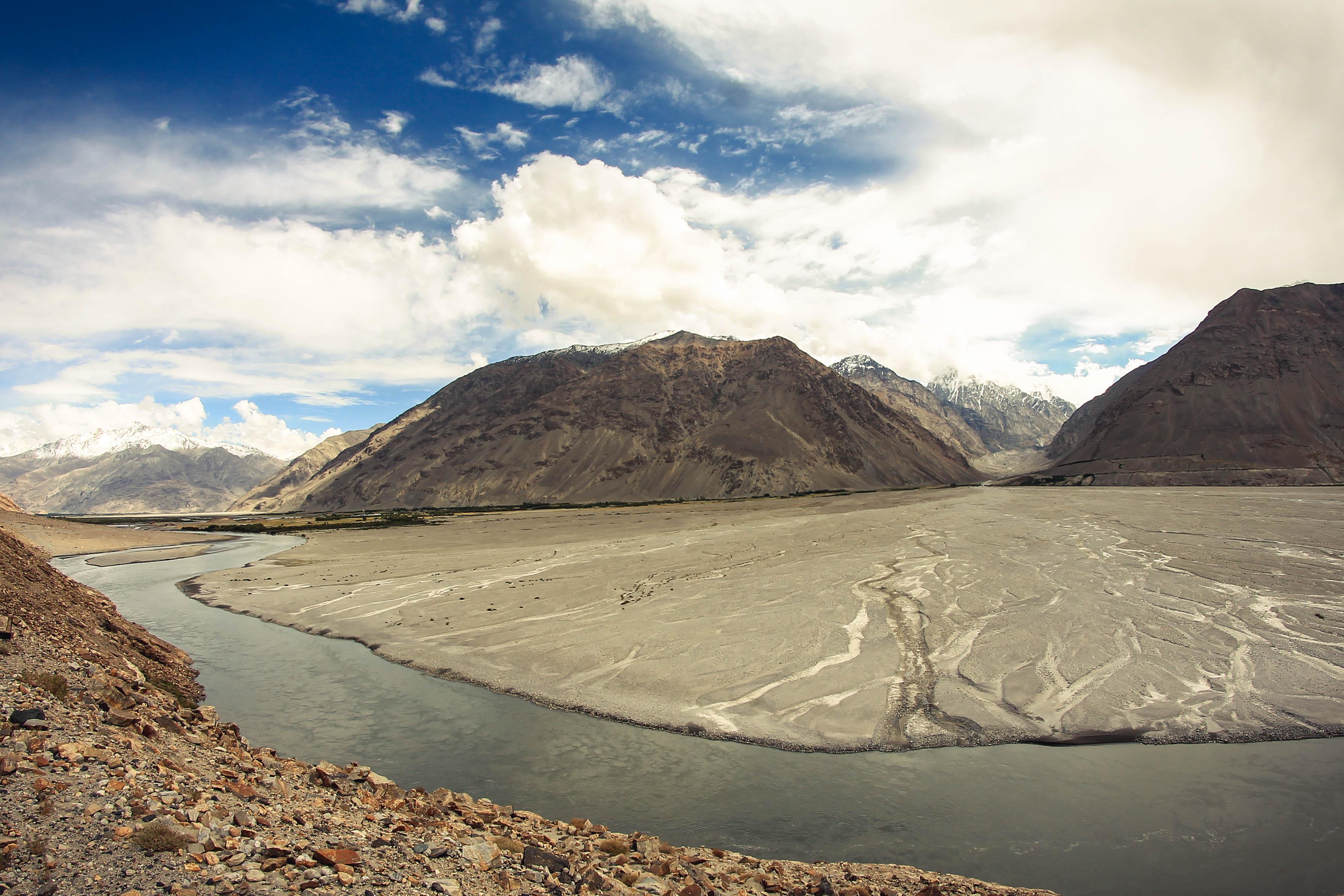 Rozlewająca się rzeka Pandż i Afganistan po drugiej stronie.